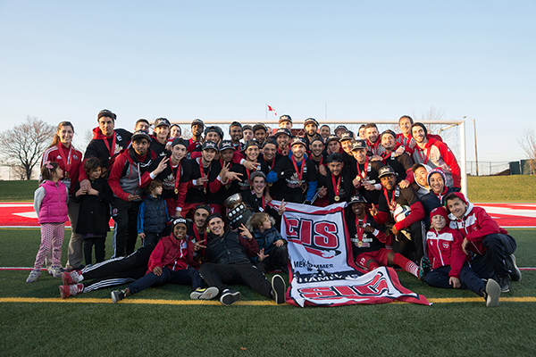 The York University Lions Men's Soccer teams pose with the provincial banner after winning the championship